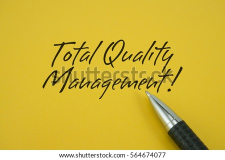 Total Quality Management! note with pen on yellow background