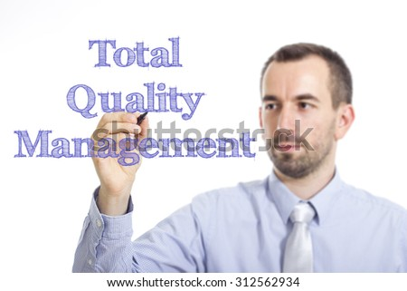 Total Quality Management - Young businessman writing blue text on transparent surface