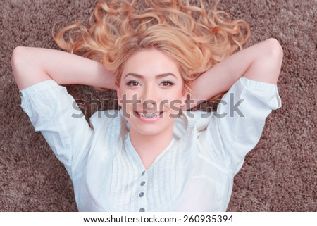 Total relaxation.  Attractive young smiling woman lying on the carpet and looking at camera - stock photo