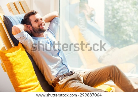 Total relaxation. Cheerful young man holding head in hands and smiling while sitting in the rest area of the office - stock photo