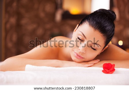Total relaxation. Front view of beautiful young shirtless woman lying on massage table and keeping eyes closed