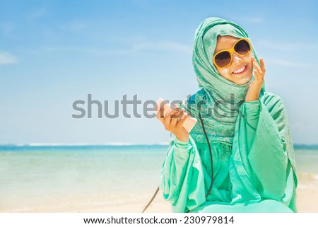total sun protection concept: pretty girl on a beach wearing traditional muslim costume - stock photo