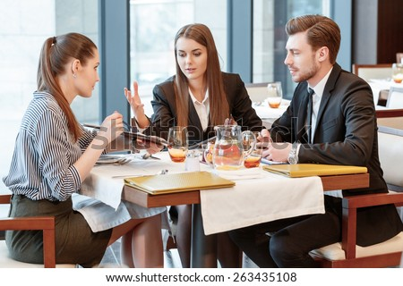 Totally disagree. Business managers have an active discussion of the business data during the lunch at the restaurant - stock photo