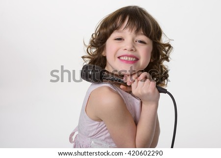 Totally happy child holds black microphone in her hands. Young princess has a beautiful smile full of positive and pleasant emotions. Close-up portrait of little brunette who loves to sing. - stock photo