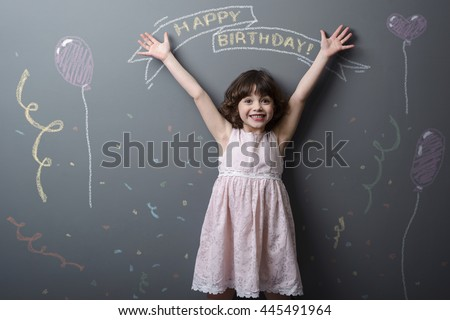 Totally happy little girl with adorable smile and rised hands looks in the camera. Pictured with chalk congratulations with birtday, confetti and toy balloon on neutral background. - stock photo