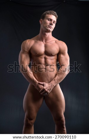 Totally naked male bodybuilder hiding genitalia with hands, looking at camera, on dark background - stock photo