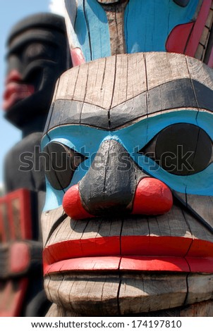 Totem poles are monumental sculptures carved from large trees, mostly Western Red Cedar, by cultures of the indigenous peoples of the Pacific Northwest Coast of North America. - stock photo