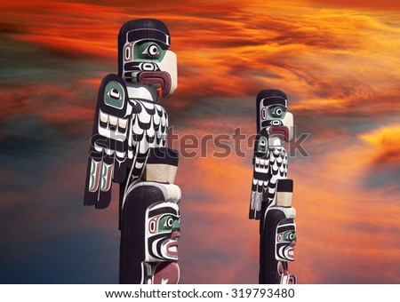 Totems with apocalyptic clouds in Courtenay, Vancouver Island, Canada - stock photo