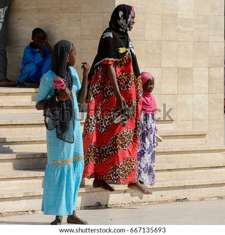 TOUBA, SENEGAL - APR 26, 2017: Unidentified Senegalese people in long traditional clothes walk in the Great Mosque of Touba, the home of the Mouride Brotherhood