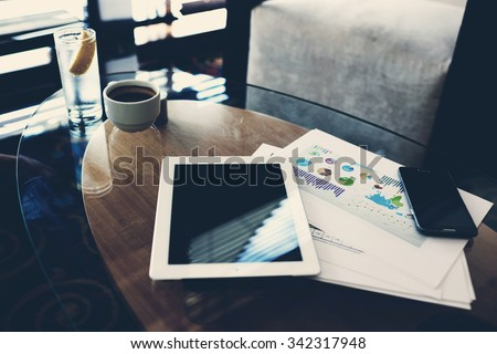 Touch pad and cell telephone with copy space screen for your text message or advertising content, digital tablet and mobile phone lying on a glass table near paper documents in office interior  - stock photo