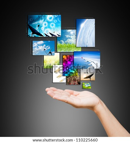 touch pad PC and streaming images buttons on women hand on background black - stock photo