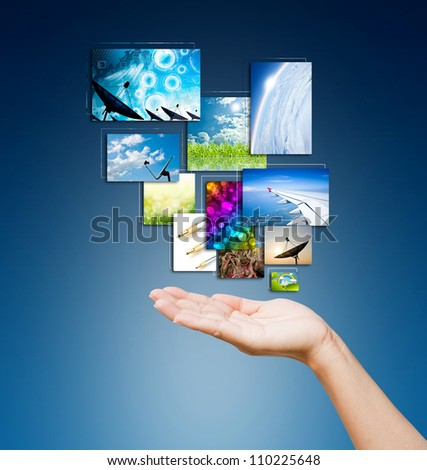 touch pad PC and streaming images buttons on women hand on background blue - stock photo