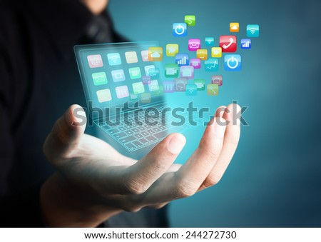 Touch screen laptop with colorful application icons in businessman hand - stock photo