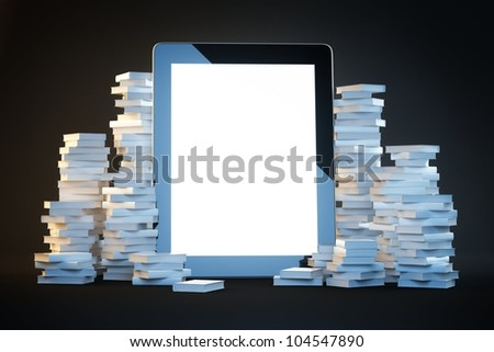touch screen pad on a black background among the many paper books - stock photo