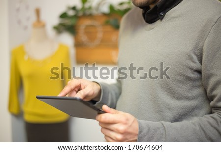 Touching a screen of a digital tablet in a fashion store - stock photo
