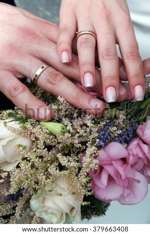 Touching hands of the bride and the groom with wedding rings on wedding bouquet background