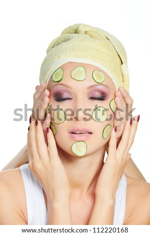 Touching hands to face of lovely woman with cosmetic cucumber mask - stock photo