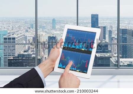 Touching stock market graph on a touch screen tablet. Trading on stock market concept.  - stock photo