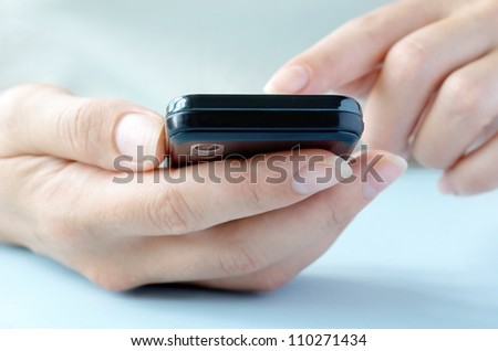 touchscreen phone in the hands of a young girl - stock photo