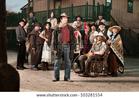 Tough cowboy with group of people in old west costumes - stock photo