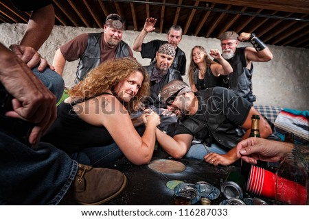 Tough grinning woman defeats biker in arm wrestling contest