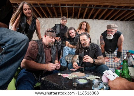 Tough group of criminals playing cards and drinking