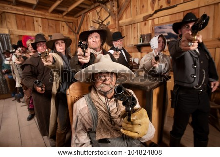 Tough group saloon customers aim their weapons straight ahead. Focus is on gun barrel. - stock photo