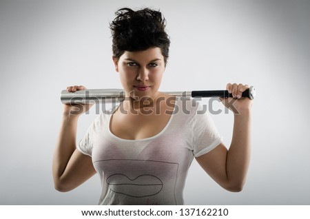 Tough looking girl with black hair and t-shirt holding a baseball bat across her shoulders - stock photo
