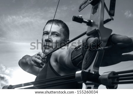 Tough man with bow and arrows, close up with cloudy sky at background. Monochromatic - stock photo
