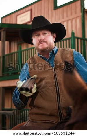 Tough old west cowboy on horseback with shotgun - stock photo