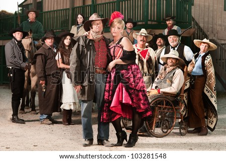 Tough old west gangster with prostitute and group of people - stock photo