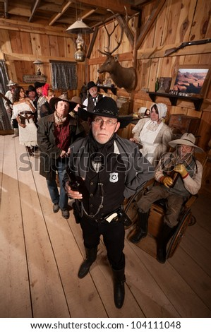 Tough sheriff with sad customers in old American west saloon - stock photo