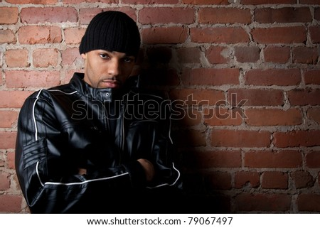 Tough street guy with his arms crossed, leaning against the brick wall. - stock photo