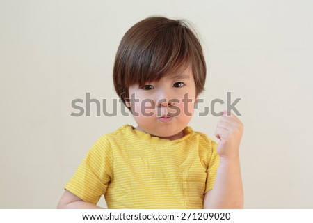 Tough toddler shaking fist. Terrible two year old. Small child punching, hitting with pout on his face. Little boy with a big attitude. Moody kid. Tantrum throwing preschooler, ready to fight. - stock photo