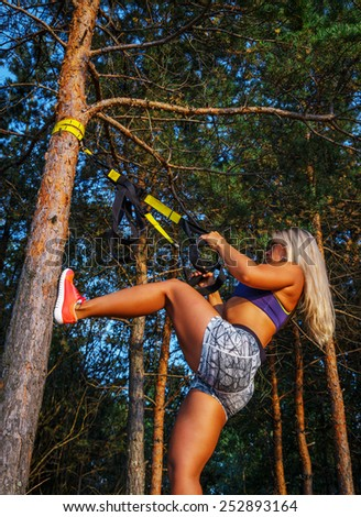Tough young woman in sports clothing doing fitness in the forest. Pine trees and blue sky on the background. - stock photo