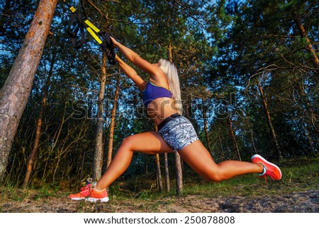 Tough young woman in sports clothink doing fitness in the forest. Pine trees and blue sky on the background. - stock photo