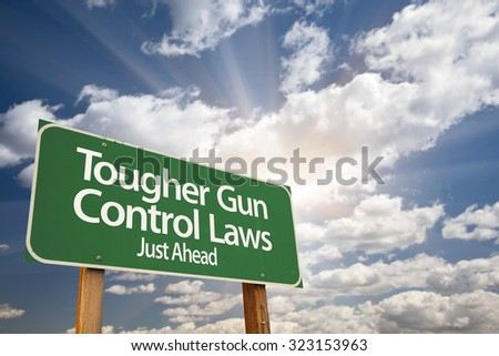 Tougher Gun Control Laws Green Road Sign With Dramatic Clouds and Sky.