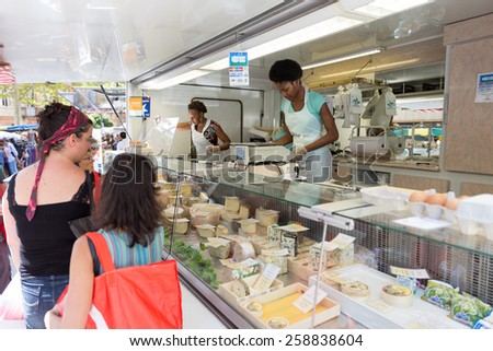 TOULOUSE, FRANCE - JULY 27, 2014: A vendor selling cheese at the March Saint Aubin, the Saint Aubin Market, in Toulouse. Marche Saint Aubin is only held on Sundays. - stock photo