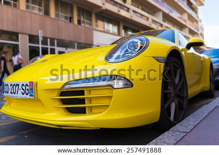 TOULOUSE, FRANCE - JULY 22, 2014: Parked bright yellow Porsche 911 with characteristic oval shaped headlights.