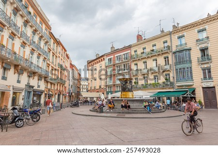 TOULOUSE, FRANCE - JULY 21, 2014:  Place de la Trinite owes its name to the convent of the Trinity. In 1826 they installed a fountain, work of Urbain Vitry, taking water from the Toulouse water tower. - stock photo