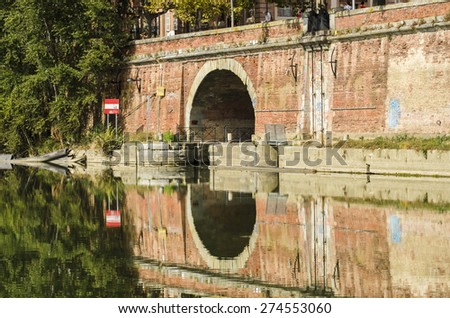TOULOUSE, FRANCE - OCTOBER 4, 2014: A man observes one of the entrances to one of the waterways of the Garonne river.