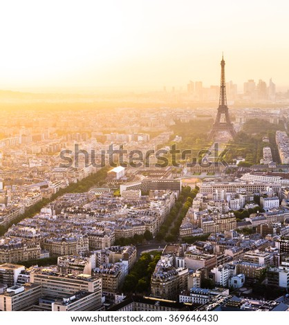 Tour Eiffel in top right of frame with skyline of Paris, France during colorful sunset with orange light - stock photo
