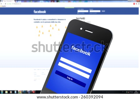 Tourin, Italy - March 14, 2015: Image of Facebook webpage on smartphone and laptop. As of today, Facebook is the largest social media network on the web, March 14, 2015 in Tourin, Italy - stock photo