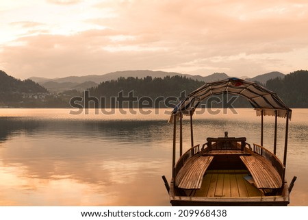 Touring boat (pletna) on famous Lake Bled, Slovenia at sunset - stock photo