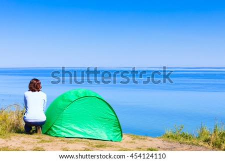Tourism and recreation. Small green tent in natural area surrounded by meadow water sea lake. Woman spending time on fresh air. - stock photo