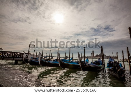 Tourism and sightseeing, gondolas laid up in line in Venice close of business at evening - stock photo