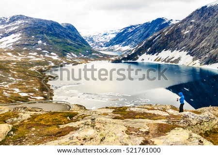 Tourism holidays and travel. Woman tourist taking photo with camera, enjoying Djupvatnet lake view in Stranda More og Romsdal, Norway Scandinavia.