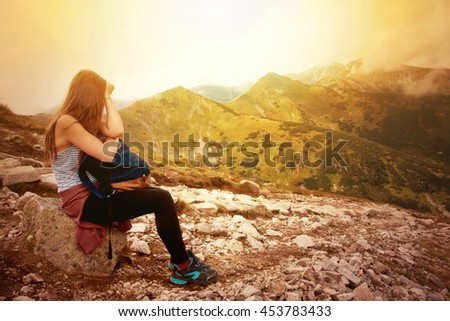 Tourism in mountains. Female tourist rest on the mountain path. Nature in mountains image.