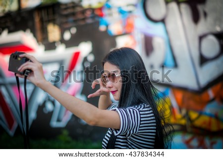 tourism, travel, leisure, holidays and friendship concept - smiling teenage girls with camera outdoors - stock photo