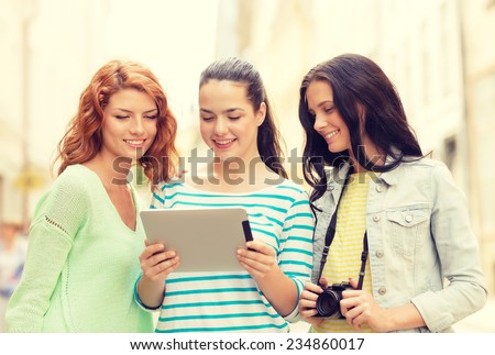tourism, travel, leisure, holidays and friendship concept - smiling teenage girls with witch tablet pc computer and camera outdoors